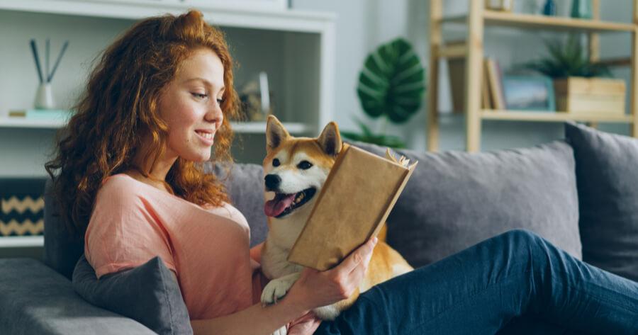 mujer leyendo un libro a su perro