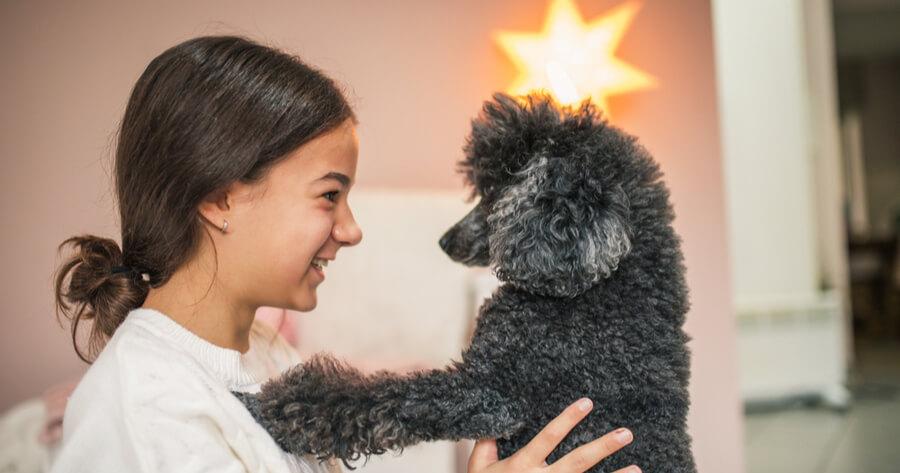 nina coge en brazo a su perro negro para hablarle