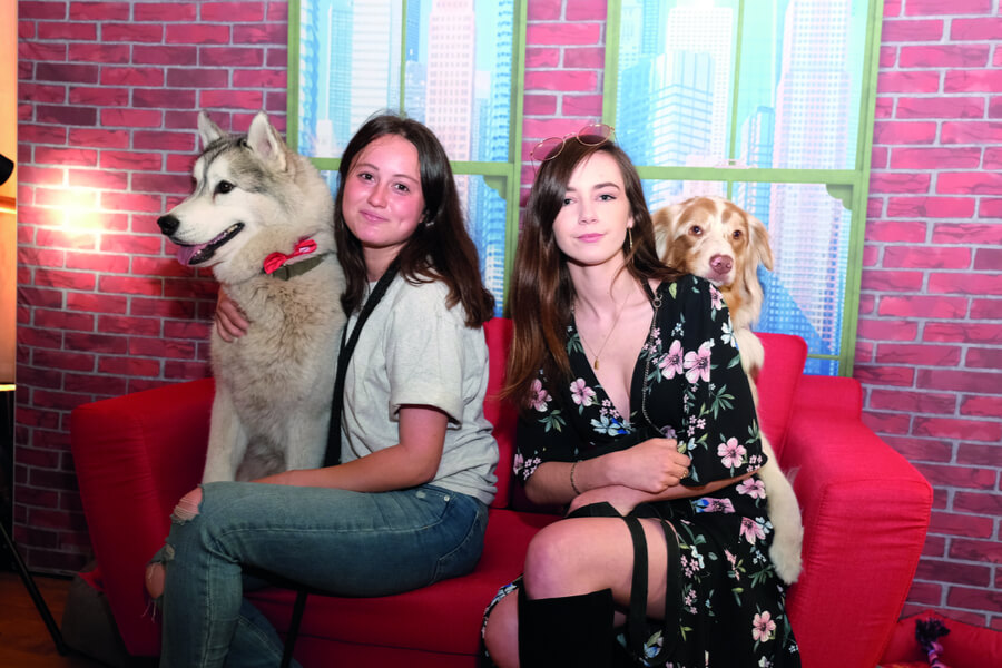 Girls sitting on sofa with dogs