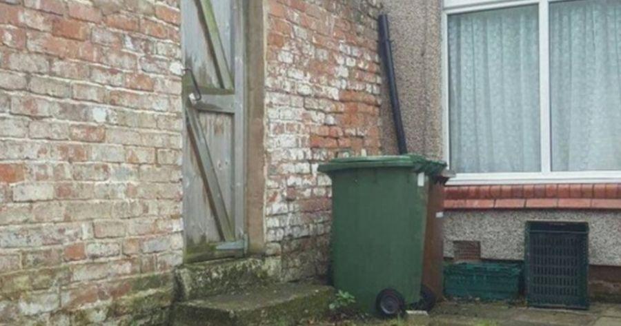 Backsteinhaus und Mülltonne