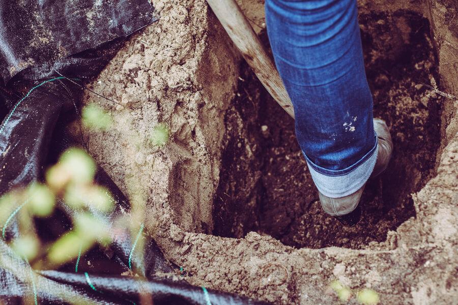Mann gräbt Grab