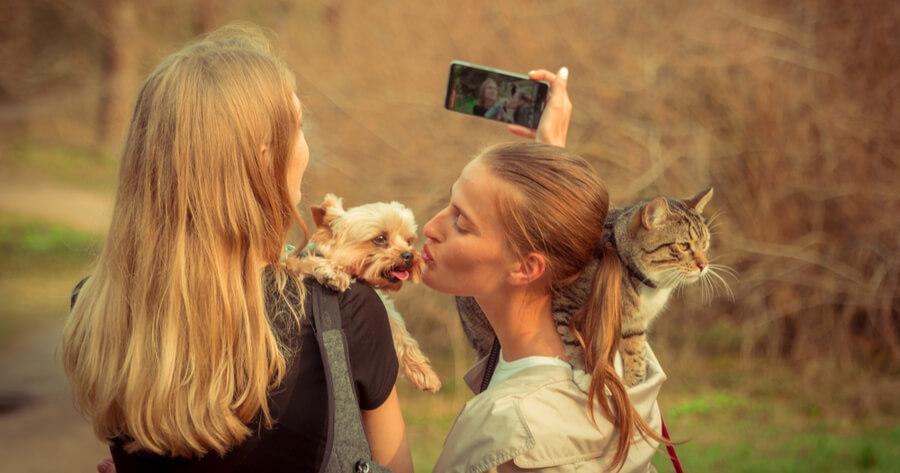 una chica con un perro en brazos y otra chica con un gato al hombro se hacen un selfie