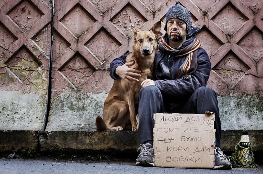mendigo abraza a su perro en la calle