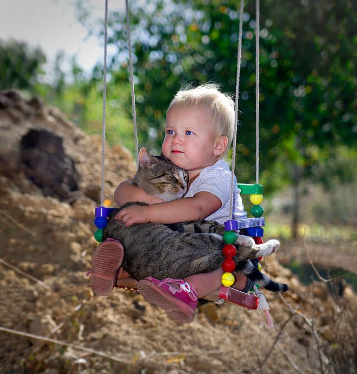 niño y gato en columpio