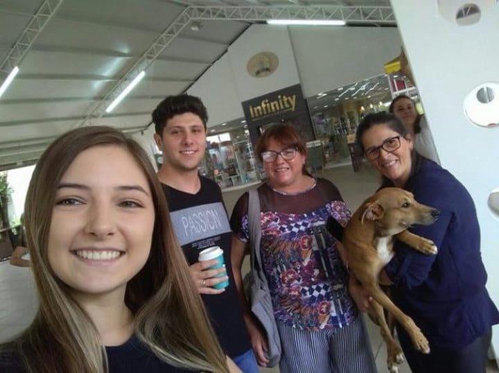 alumnos y trabajadores de la biblioteca con el perro en brazos