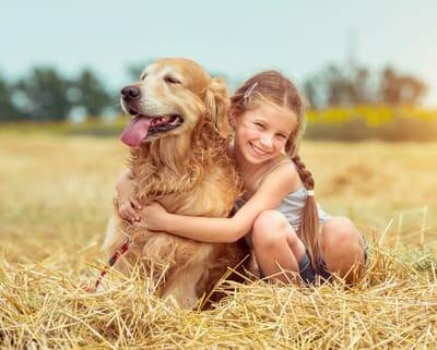 golden-retriever-con-bambina-sorridente-sulla-paglia