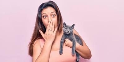 ragazza si copre la bocca con la mano con in braccio un gattino grigio