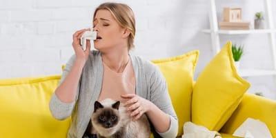 donna allergica al gatto seduta sul divano