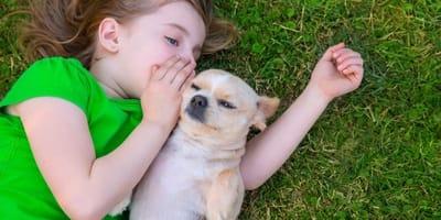 bambina-bionda-parla-allorecchio-di-un-cucciolo-beige.jpg