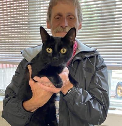 gata negra en brazos de un hombre