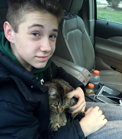 adolescente con un gato sobre su regazo en un coche