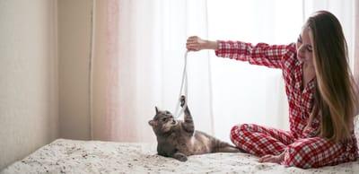 mujer juega con gato listón