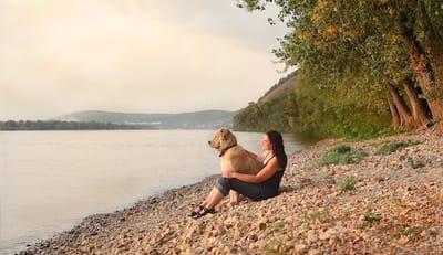Cane con la padrona davanti a un lago