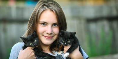 ragazzina con due gattini neri