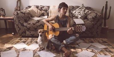 Cane accanto a padrona che suona la chitarra