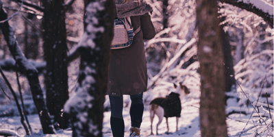 girl walking her dog in the forest in Winter
