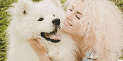 Girl with curly white hair hugging her white samoyed