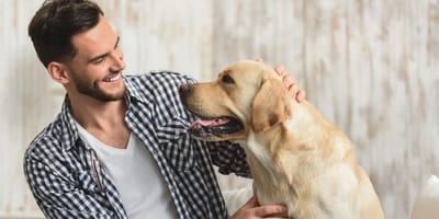 junger mann lacht und streichelt hund