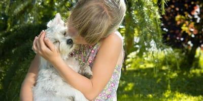 Bimba che bacia il suo cane bianco