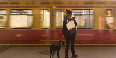 Frau mit Hund vor U-Bahn in Berlin