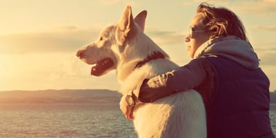 Frau mit Hund am Meer