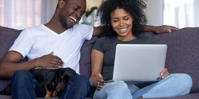 Frau, Mann und Hund vor Laptop/Onlinekauf von Hund