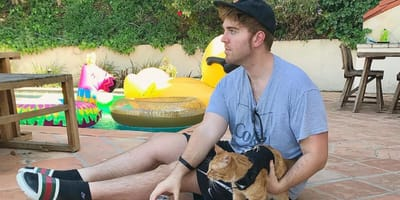Shane Dawson sitting on patio with cat
