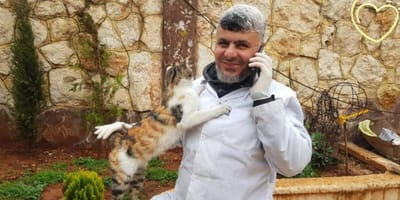 A doctor employed by Aleppo cat sanctuary holds cat