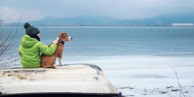 Frau mit Hund in winterlicher Landschaft