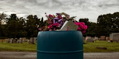 bin in cemetery with trash