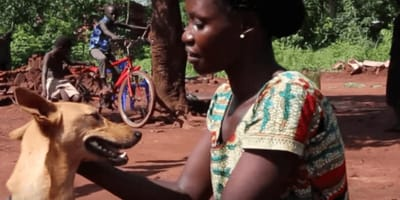 Ugandan woman petting dog