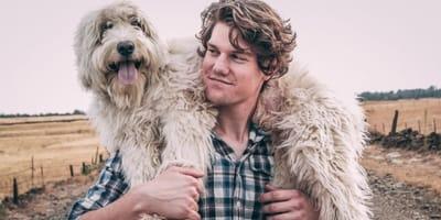 uomo con cane sulle spalle