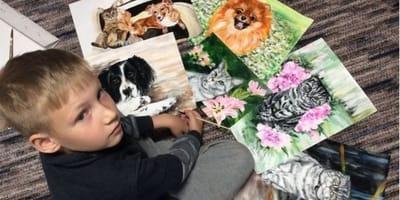 bambino seduto a terra con dipinti di animali eseguiti da lui stesso