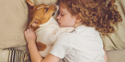 Ginger girl asleep in bed with dog