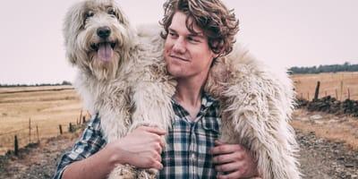 Mężczyzna niosący na plecach psa