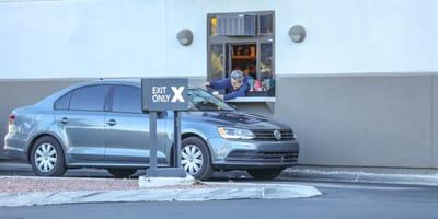 Frau streckt Becher zum Auto am Drive-Fenster