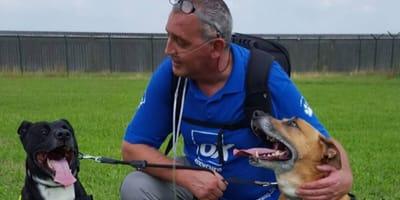 man breathing through tubes smiles at his dogs