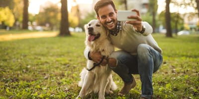 Man taking a selfie with golden retriever dog