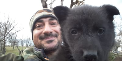 black puppy in bearded owner's arms