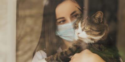 Frau mit Mundschutz und Katze