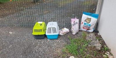 Zwei Katzenkörbe und Futter vor einem Zaun