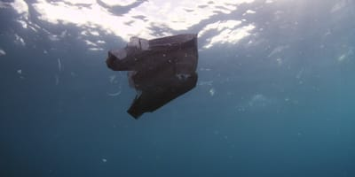 bolsa negra flotando en el mar