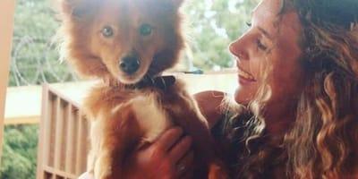 ragazza sorride guardando il cagnolino in braccio