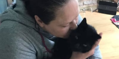 black cat kissed by owner
