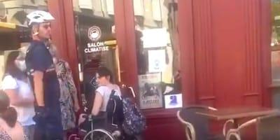 donna su sedia a rotelle davanti a un bar