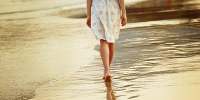 woman in summer dress walking on the beach