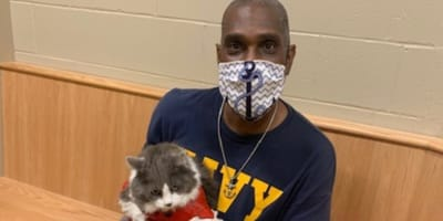 man wearing mask holding white and grey cat