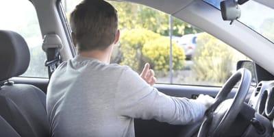 hombre mira hacia atras en un coche