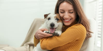 woman holding her Jack Russell Terrier dog