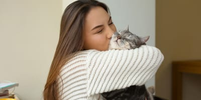 woman kissing and holding grey tabby cat